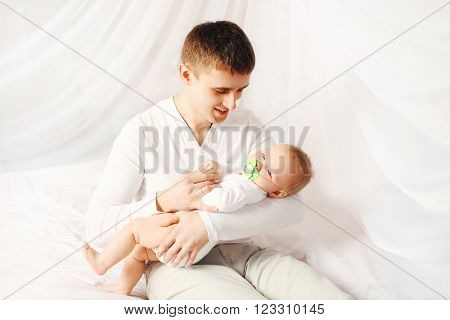 Happy Father With Baby On Bed At Home Bedtime