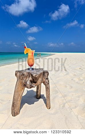 Bocal of cocktail is on original beach table is made from trunk of tree