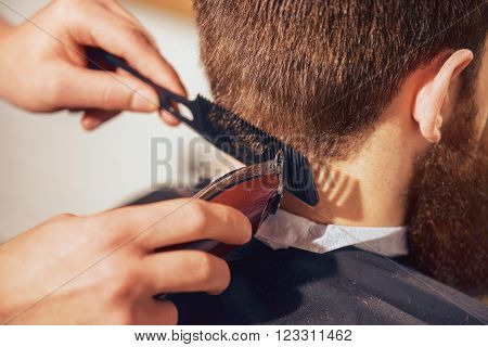 Professional barber holding comb and razor while cutting hair of his client.