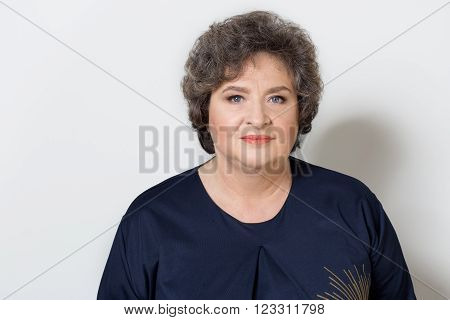 Portrait of a beautiful elegant old woman with light make-up in the studio on a white background