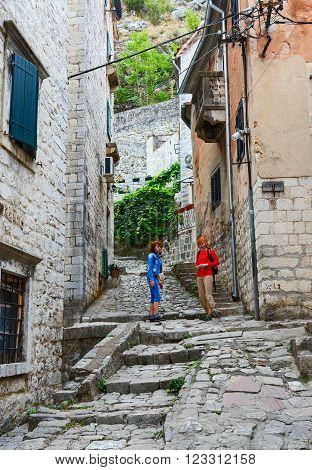 KOTOR MONTENEGRO - SEPTEMBER 21 2015: Unidentified tourists climb along a narrow street of the Old town to the fortress Kotor Montenegro
