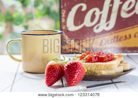 Coffee with milk and toast with strawberry jam