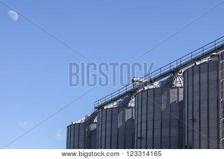 Storage tanks for cereals products over blue sky with moon