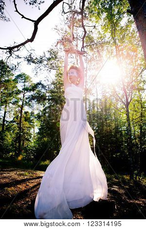 a young girl in a white dress and a blindfold in the woods riding on the bungee