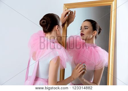 Beautiful young woman in white bodysuit and pink basque standing near wall mirror