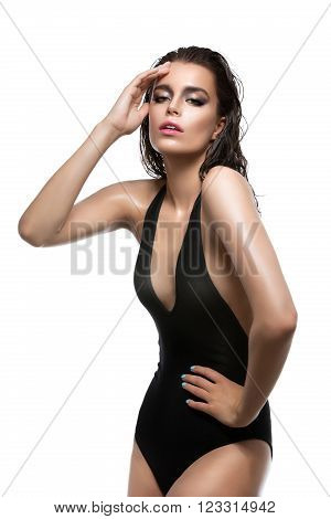 Beautiful wet young woman in black sexy swimwear. Isolated over white background. Copy space.