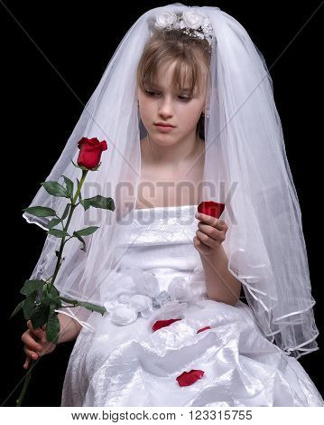 Very young bride. Wedding white dress. Luxury veil. Flower red rose. Background black. Bride sad. A minor child. The concept of the wedding teens
