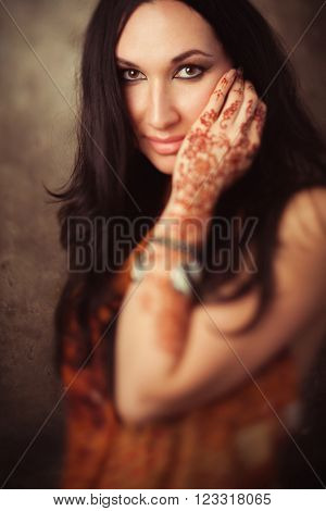 Tender indian woman in traditional clothing with mehndi on hand. Playful indian girl in  sari with mehndi. Beautiful lady in indian dress