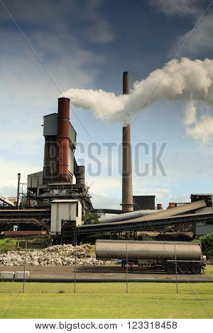 Steel mill smelter emitting toxic fumes and air pollutants billowing up and out of one of its many tall chimneys.