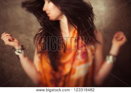 Indian woman with long hair in motion against stone background. Activity of indian woman with flying long hair. Defocused foto of dancing indian girl with blowing hair.