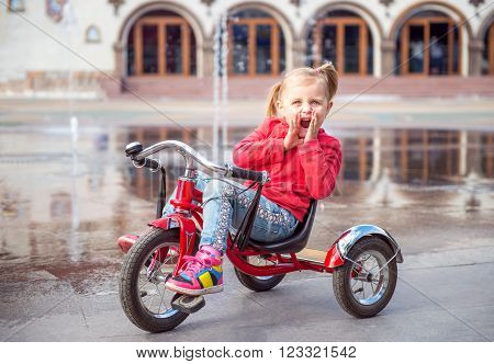 Little girl in amusement park near fountain riding on tricycle and screaming