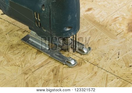 Old electricsaw cutting a sheet of OSB