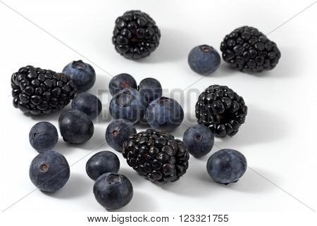 Blueberries and blackberries on white background
