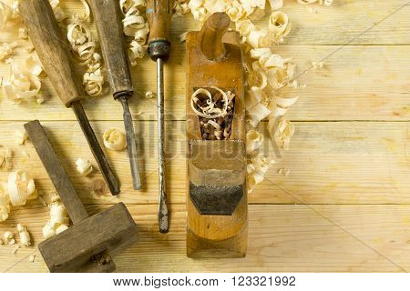 Carpenter tools on wooden table with sawdust. Craftperson workplace top view.