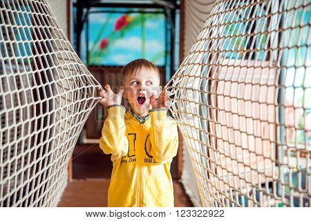 Little boy in yellow hood is very amazed in amusement park with rope walls