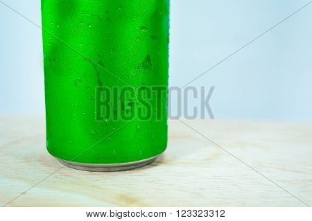 Drink chilled cans green and with water drops attached. There is a wood background focus water drops.
