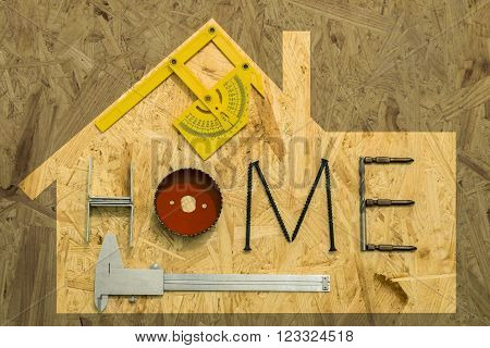 The concept of home renovation. Fixing materials and tools on a sheet of OSB, the frame in the shape of a house.