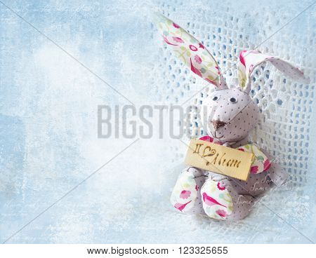 Cute hare. Happy Mother's Day bunnie holding board with the inscription I love mum. Greeting card for Mother's day.