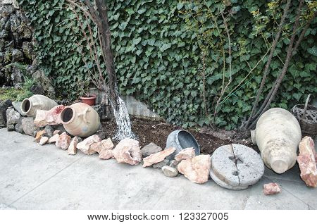 Old millstones,jug, pot,with stones onyx and basalt in the yard about walls covered green plush
