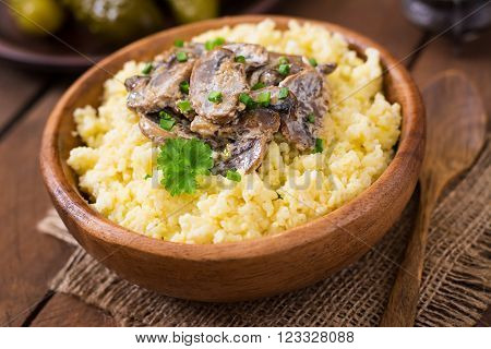 Millet porridge with mushrooms in a wooden bowl