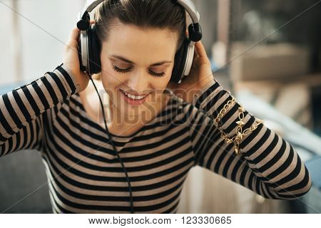 Woman Listening To Music In Loft Apartment. Close Up Portrait.