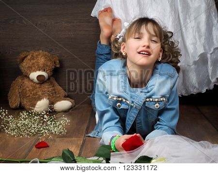 Girl teenager treats wedding accessories. Girl lying on the floor in jeans and barefoot. In the frame of a wedding dress, a teddy bear, a box for an engagement ring