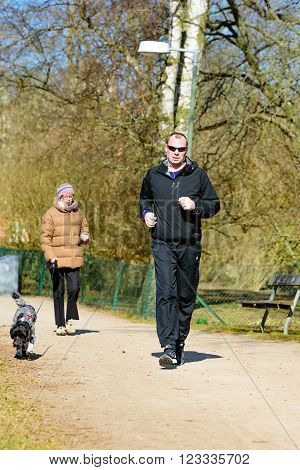 Kristianstad Sweden - March 20 2016: A male person running in the park passing a female dog handler with her dog. A sunny spring day with real people in everyday life.