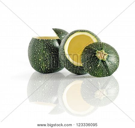 Two eight ball squash with cut top and scooped out pulp isolated on white with reflection.