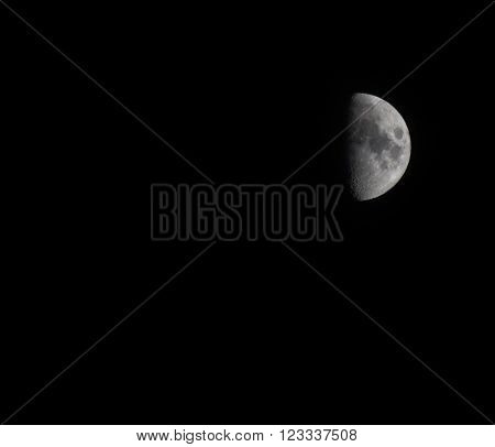 Half moon on black night sky. Earth satellite