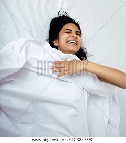 pretty indian brunette real woman in bed smiling, white sheets, tann skin close up mulatto. cant sleep, fooling around