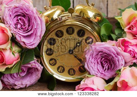 bouquet of pink and violet fresh roses with vintage clock.