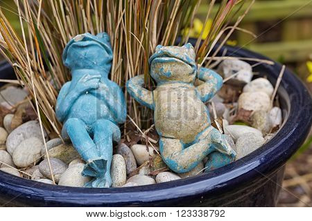 Two relaxing blue and beige garden frogs figures lying in a plant pot as a garden decoration artificial toy