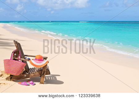 Chair with bag hat flip-flops and sunglasses on sunny beach tropical beach vacation and travel concept
