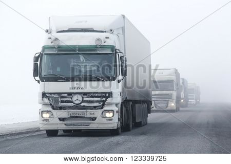 BASHKORTOSTAN, RUSSIA - FEBRUARY 7, 2016: Semi-trailer truck Mercedes-Benz Actros at the interurban freeway during a heavy fog.