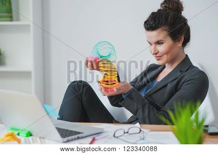 Attractive young woman calms down playing with a toy spiral. She is sitting in her office and relaxing. The woman is smiling