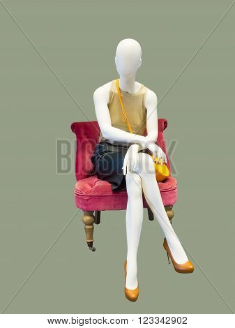 Female mannequin sitting on red armchair, against grey background. No brand names or copyright objects