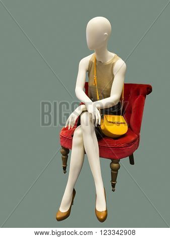 Female mannequin sitting on red armchair against green background. No brand names or copyright objects.