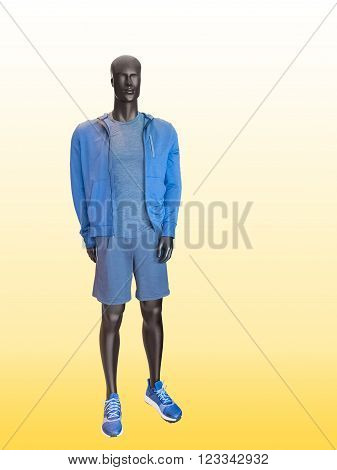 Male mannequin wearing clothes for sport end rest over yellow background