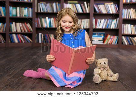 Playful childhood. Little girl having fun at room with bookshelf. Girl reading book