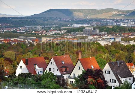 STUTTGART, GERMANY - APRIL 22, 2014: Panorama of Stuttgart. Private homes in the foreground the amusement park and the mountains in the background. Baden-Wuerttemberg, Germany.