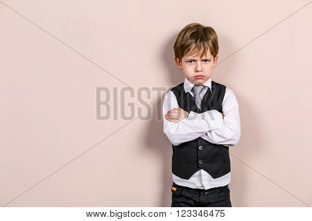 Little boy wearing school uniform. Boy is bored and upset. Boy looking at camera