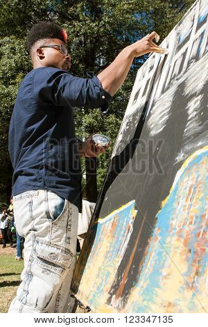 ATLANTA, GA - OCTOBER 17 2015:  A young artist uses his fingers to paint a canvas at the Elevate Art festival in Atlanta, GA on October 17, 2015.