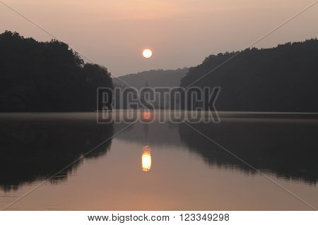 beautiful landscape during sunrise on the lake, the sun's reflection in the water and the shade of trees