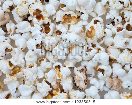 Popped corn on the paper background close up.
