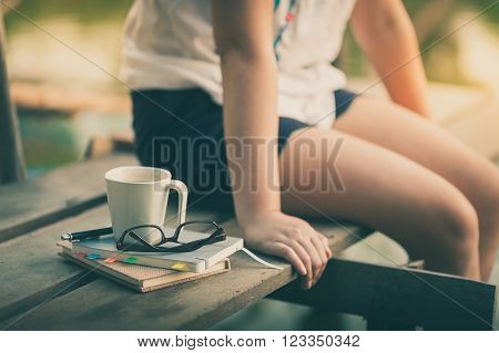 Notebooks pen glasses and coffee cup are putting down on the wood waterside while young woman sitting beside them in morning time on weekend with vintage filter effect