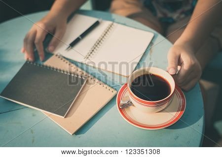 Woman left hand holding coffee cup during coffee break in cafe with morning scene and vintage filter effect