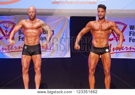 MAASTRICHT THE NETHERLANDS - OCTOBER 25 2015: Male bodybuilder Erik Stobbe with fellow competitor show their best front pose at the World Grandprix Bodybuilding and Fitness of the WBBF-WFF on October 25 2015 at the MECC Theatre in Maastricht