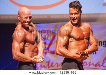 MAASTRICHT THE NETHERLANDS - OCTOBER 25 2015: Male bodybuilder Erik Stobbe with fellow competitor show their best chest pose at the World Grandprix Bodybuilding and Fitness of the WBBF-WFF on October 25 2015 at the MECC Theatre in Maastricht