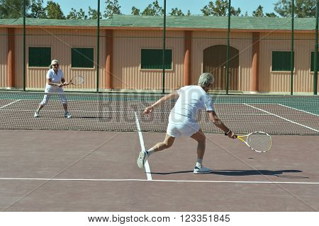 Portrait of active senior couple on tennis court
