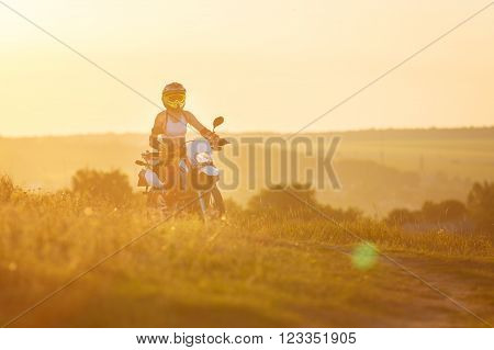 Woman biker rides in fields. Sporty woman biker at motobike. Countryside, country road.  sunset, female motorcycle rider, motorbike rider traveling the world, girl resting, freedom lifestyle